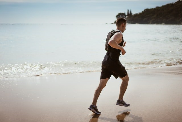 Muž bežiaci po pláži