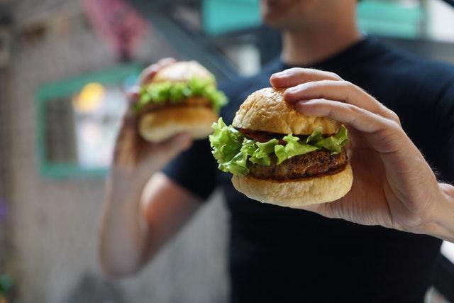 Muž držiaci hamburgery