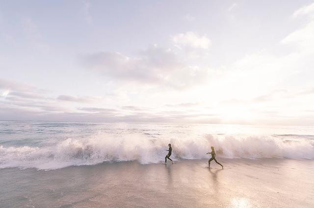 Dvaja ľudia sa naháňajú na pláži pri vlnách.jpg