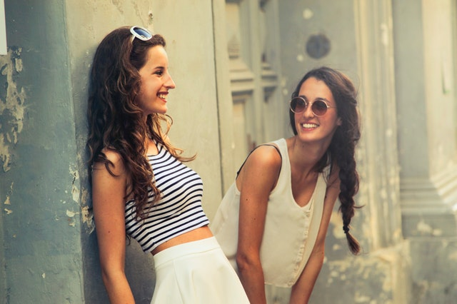 Dve štíhle usmiate ženy pri budove.jpg
