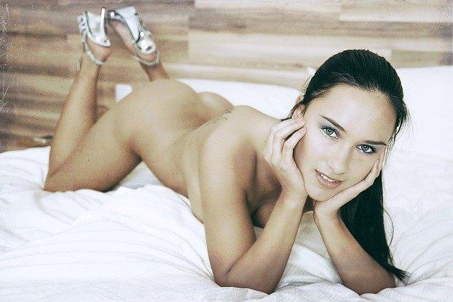 Nahá žena so striebornými topánkami v posteli